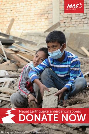 2 Nepalise children sit atop a pile of rubble following the earthquake.