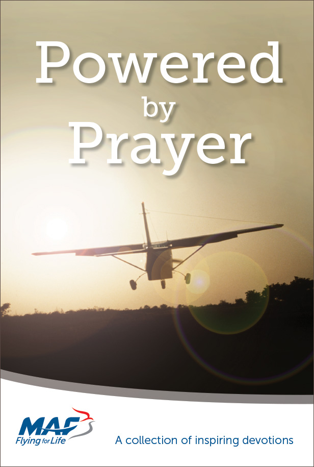 Powered by Prayer front cover. Silhouette of a plane flying into a sunset.