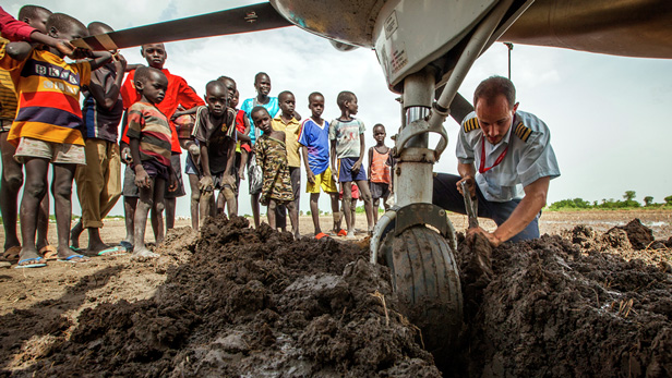 Pilot Ryan Unger works to free his plane from the mud in Leer, South Sudan.