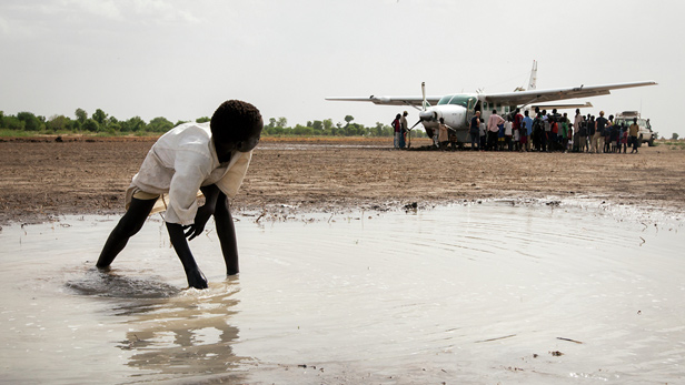Children watch as villagers and passengers gather round an MAF plane.