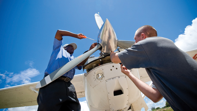 Technicians Ben Kulwa and Martijn Verboom working on a Cessna 206.