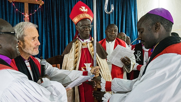 Retiring Bishop of Marsabit Robert Martin performs the Presentation of the Pastoral Staff to newly appointed 2nd Bishop of Marsabit Diocese at the Consecration and Enthronement Ceremony