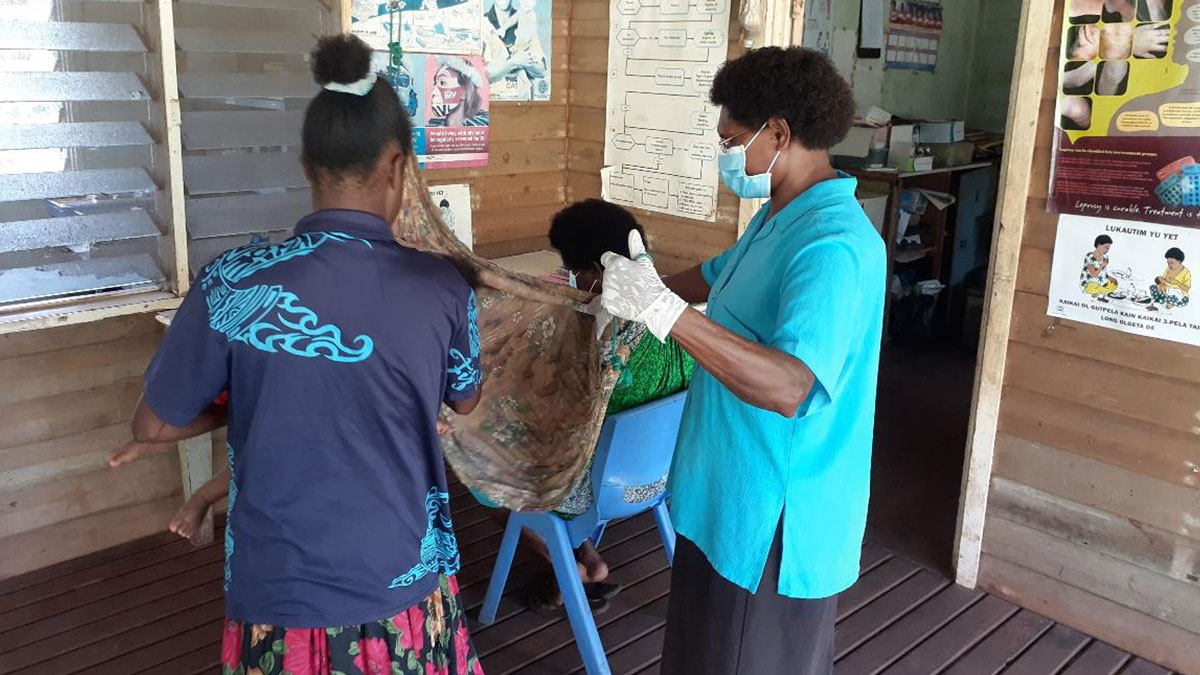 Nurse wearing new PPE treating patients at Moreland Clinic in PNG