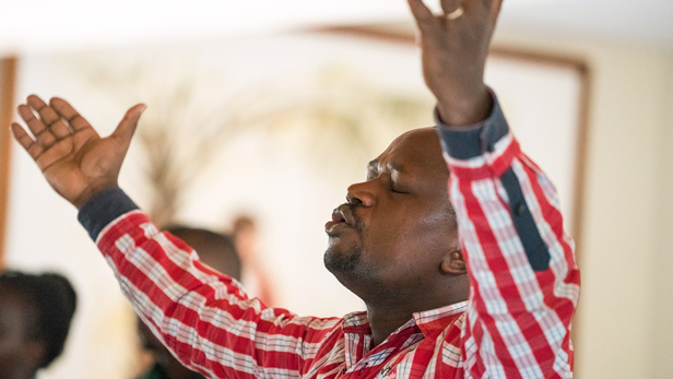 A man lifting his arms in worship.
