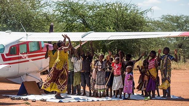 Under the MAF plane wing, Mama Ruth Kambenga and 17-year-old Peter Daniel sing with and teach the local children from nearby villages while on the Kilimatinde Medical Safari taking place at Chidudu, Tanzania.