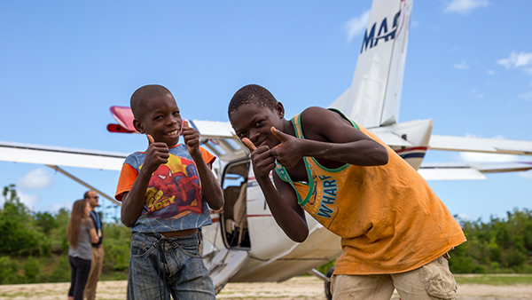 Children pose in front of an MAF Kodiak in Jeremie, Haiti