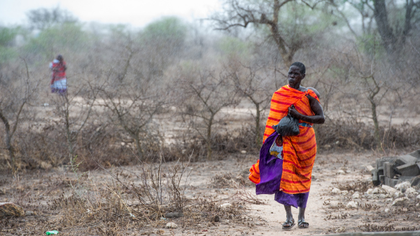 A Massai woman is walking through the rain in Kitwai, Tanzania