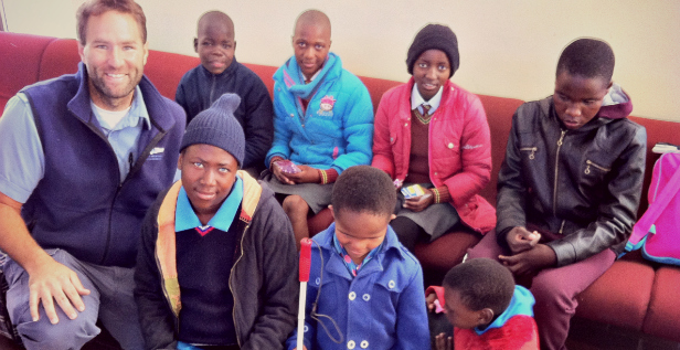Pilot Bryan Eygabroad with Neheng (back row, light blue jacket), next to Sebongile (in red), and other children being flown to a special school session.