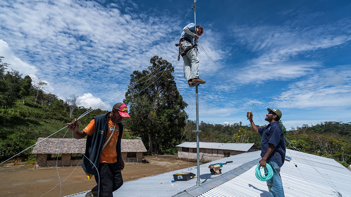 Joey Redhead (C) & David Feka (R) install an antenna on the roof of a remote primary school in PNG