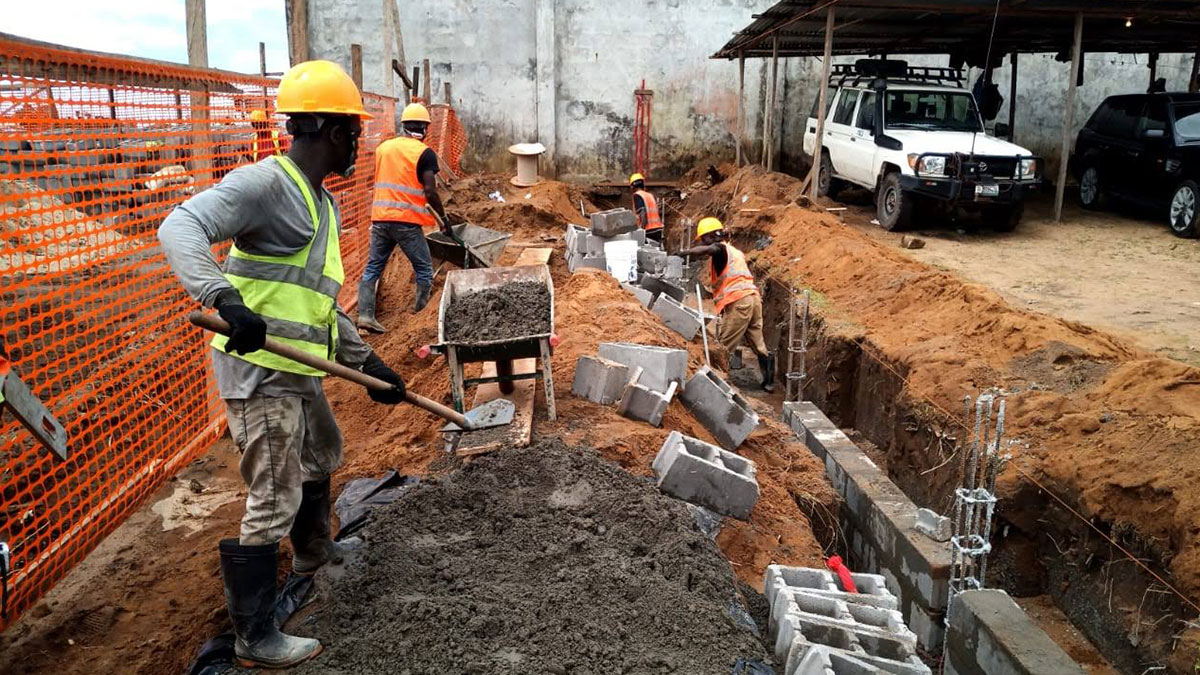 Four builders constructing rear security wall for MAF's new hangar in Monrovia