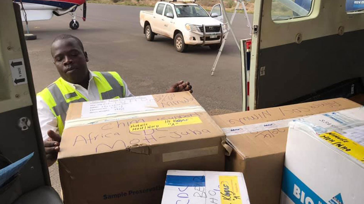Worker loading up coronavirus testing kits bound for Nimule on South Sudan border