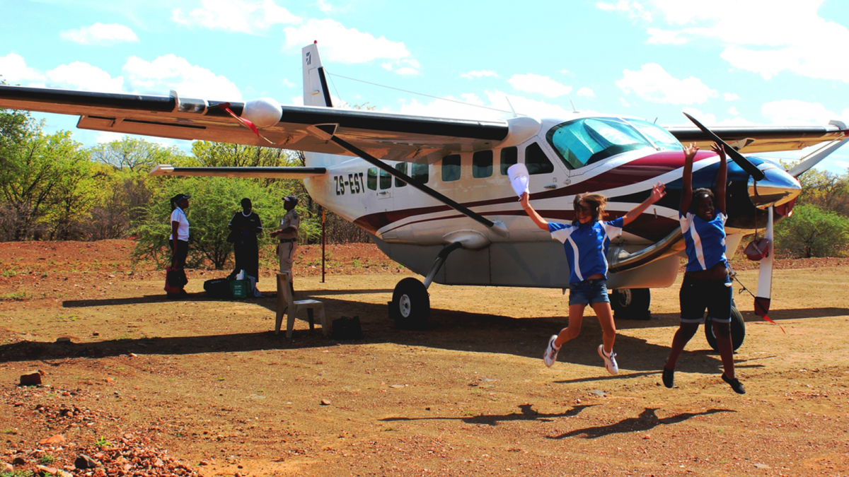 2 students leaping with excitement after MAF flew them into South Africa