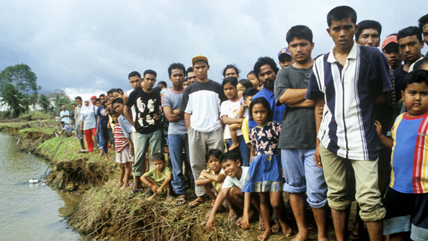 A crowd of people wait for the arrival of the Beaver Floatplane at 'Delta 21' a river north of Meulaboh.