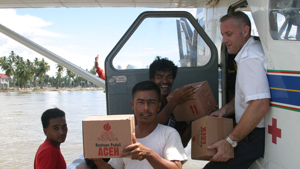 Locals help MAF staff unload a cargo full of supplies.