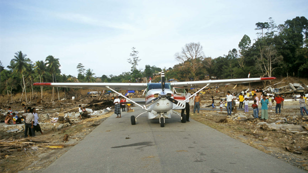A Cessna 206 lands on a stretch of road to deliver essential relief supplies.