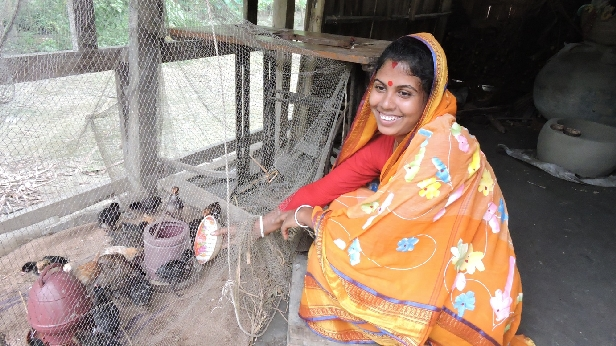Aporna Shikder with her chickens. Aporna received training in Bangladesh at the USAID-sponsored Farmer Nutrition School