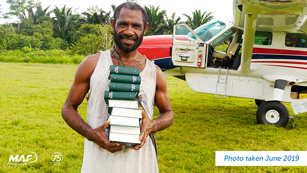 Papua New Guinean man holds a stack of Bibles - posted 4 April 2020