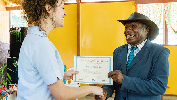 Thomas Makinsa, an elder at the church and the oldest student at 63 years old, receives his certificate of participation from MAF's Emma McGeorge