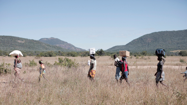 Villagers carrying food and Bibles from the airstrip to the village in Mukwando.