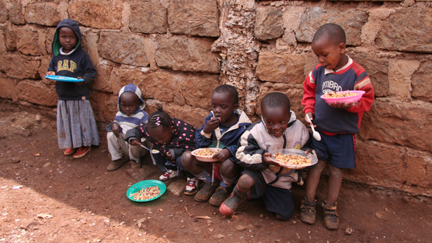 Children eat food supplied by 'Feed the Hunger' in Kurungu.
