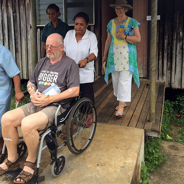 Geoff Boer, with wife Jennifer, is wheeled out of Rumginae Rural Hospital heading toward the MAF Airvan for a flight to Kiunga