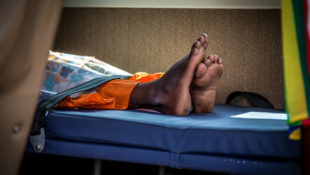 The patients legs are seen carefully strapped down to the hospital bed.