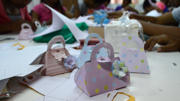 Small hand bags made from folding and sticking card, decorated with paper flowers.