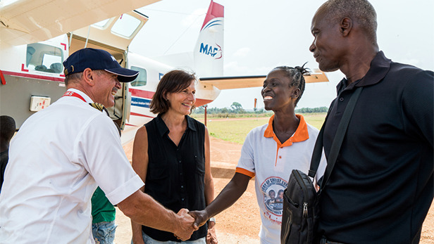 Abraham and Agnes Howard, who pastors a church and runs an orphanage in Foya, speaks to MAF pilot and Country Director Emil Kündig and wife Margrit at the Foya airstrip in Liberia. Image credit LuAnne Cadd. Copyright Mission Aviation Fellowship.