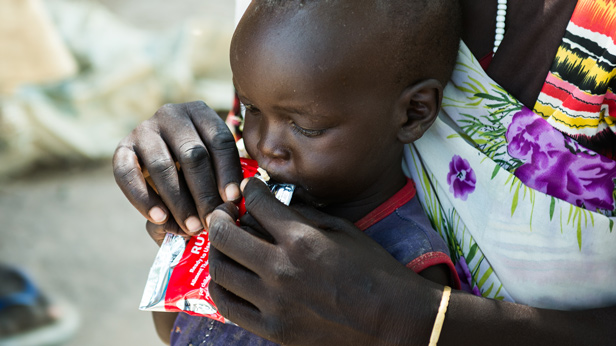 Mother and child collect Plumpy Nut supplement at Tearfund feeding center in South Sudan.