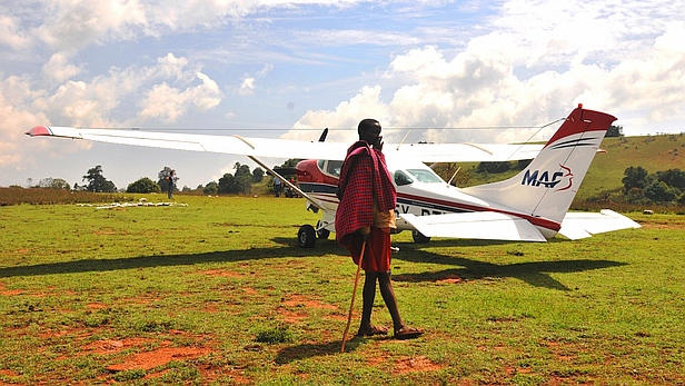Maasai person and an MAF Cessna 206 at Entesekera, Kenya