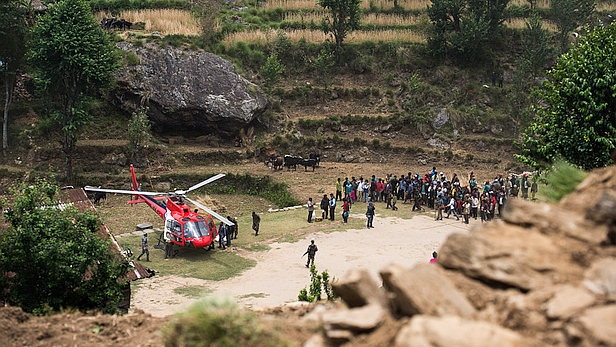 The helicopter lands and unloads rice, tarps, and other relief items at Jharlang. Photo credit: MAF/LuAnne Cadd