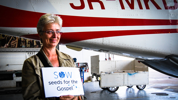 Hilde in the MAF hangar holding a 'Sow seeds for the Gospel' sign.