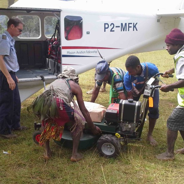 Pilot Markus Bischoff supervising locals loading the lawn mower at Eleme (RvW)
