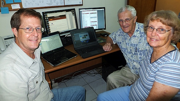 MAF's Roger Kolb (left) helps Leon and Lorraine Dillinger update their computers so they can finish working on Bible commentaries. In Papua, Indoneisa. Photo courtesy of the Kolbs