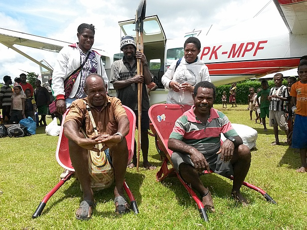 Yogele (right front) with Yusak (left) and others posing with shovels and wheelbarrows flown by MAF to aid in extending the airstrip at Derapos in Papua, Indonesia. Photo by Pieter Van Dijk