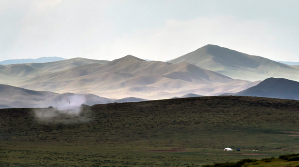 A spase mongolian landscape with rolling hills, and mountains in the distance. A single Yurt can be seen.