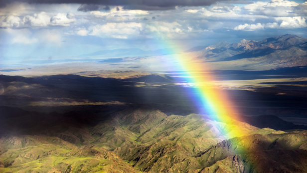 A vibrant rainbow over a mountain range in Mongolia.