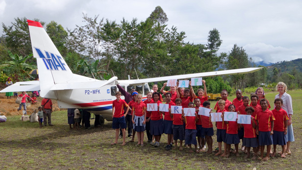Children from Kompiam International School hold up there 'MAF Marathon' sign infront of a Cessna 208.