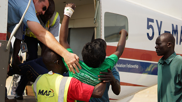 Unconscious of what is happening Manuela is lifted out of the plane and into a car at Juba International Airport.