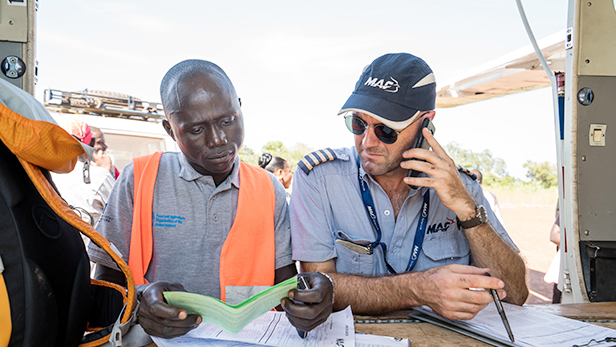 Pilot Sam Johnston lands at Mundri where he drops off and picks up passengers, completing paperwork with airport official Simon Elniah. Photo credit - LuAnne Cadd.