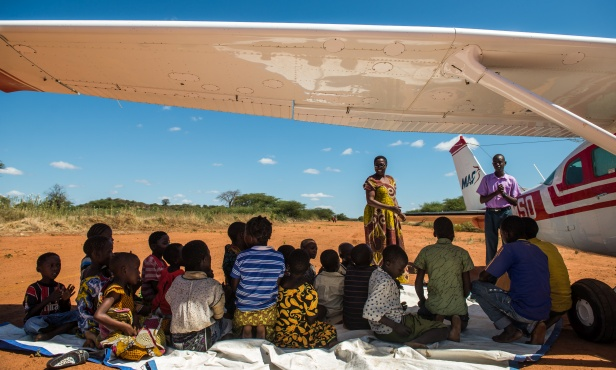 MAF-Tanzania-teaching children under the shade of an MAF aircraft wing. By LuAnne Cadd