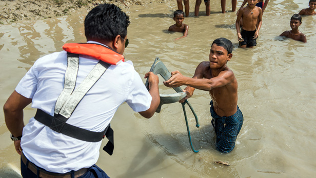 MAF's flight crew, Raju Mondal, collects an anchor from a boy on the muddy land next to the river