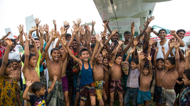 Crowds of children and adults gather to watch the float plane that landed in Bhola, Bangladesh.