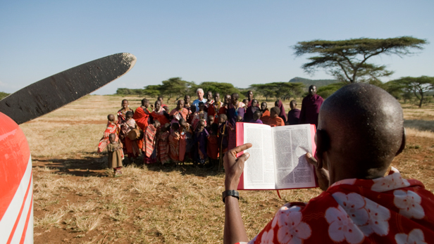 Village of Ole Milei, Malambo Safari, Evangelist Joel preaches from the Bible next to an MAF plane.